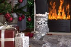 Pés da menina na posição do soquete do Natal nos dedos perto da chaminé fotografia de stock royalty free