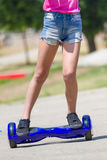Pés da menina no hoverboard azul Fotografia de Stock Royalty Free