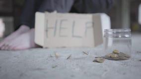 Pés da menina pobre descalça no close-up concreto do assoalho Um sinal borrado que diga a ajuda está próximo Moedas que caem no p video estoque