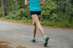 Pés da menina que corre abaixo da estrada nas madeiras Imagem de Stock Royalty Free