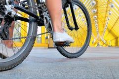 Pés da menina que senta-se pela opinião traseira da bicicleta imagens de stock royalty free