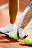 Pés da menina sportive perto da raquete de tênis foto de stock