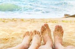 Pés da moça e do homem no mar Imagem de Stock