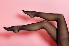 Pés da mulher caucasiano nova em calças justas pretas Fotografia de Stock