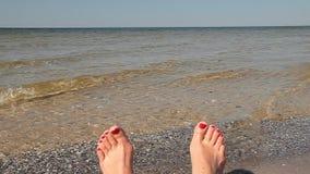 Pés da mulher com os pregos vermelhos que relaxam em uma praia com o oceano no fundo Ondas do mar do rolamento video estoque