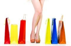 Pés da mulher com sacos de compras Imagens de Stock Royalty Free
