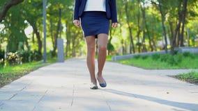 Pés da mulher de negócio nova irreconhecível no vestuário formal que anda no parque verde apenas A menina mantém a maneira de tra filme