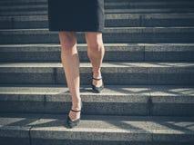Pés da mulher de negócios nova na cidade em escadas Imagens de Stock Royalty Free