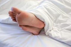Pés da mulher de sono na sala branca da cama Foto de Stock