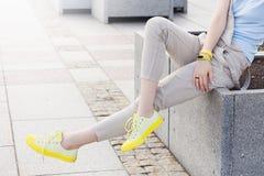 Pés da mulher desportiva nova em paisagens urbanas do verão fotos de stock
