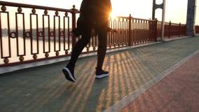 Pés da mulher do corredor que movimentam-se na ponte durante o tempo do nascer do sol Pés do atleta fêmea que correm o estilo de  filme