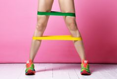 Pés da mulher do instrutor da aptidão que exercitam dar certo com a faixa de borracha verde e amarela da resistência no rosa mode imagem de stock royalty free