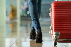 Pés da mulher do viajante que andam levando uma mala de viagem Fotografia de Stock