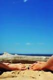 Pés da mulher e das meninas na areia na praia imagem de stock