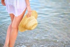 Pés da mulher e um chapéu de palha à disposição na praia na água do mar fotos de stock