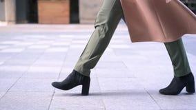 Pés da mulher em botas pretas que anda na rua video estoque