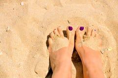 Pés da mulher na areia Imagens de Stock
