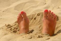 Pés da mulher na areia Imagem de Stock Royalty Free