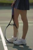 Pés da mulher na corte de tênis imagens de stock