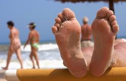 Pés da mulher na praia Fotos de Stock