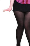 Pés da mulher na saia curta Imagem de Stock