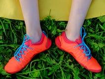 Pés da mulher nas botas do vermelho com laços azuis na grama imagens de stock royalty free