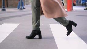 Pés da mulher nas botas pretas que cruzam a estrada vídeos de arquivo