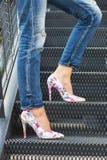 Pés da mulher nas calças de brim e nos saltos altos 'sexy' coloridos, estando em uma escadaria, fotografada do lado fotografia de stock royalty free
