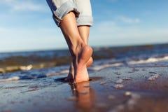 Pés da mulher nas ondas do mar Imagens de Stock