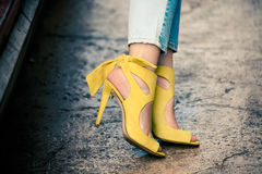 Pés da mulher nas sandálias amarelas de couro do salto alto exteriores na cidade fotografia de stock