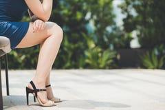 Pés da mulher no salto alto vestindo da mini saia foto de stock