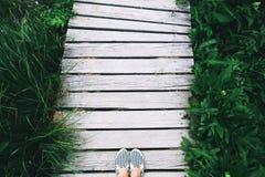 Pés da mulher nos calçados casuais no fundo de madeira do cais com GR Fotografia de Stock