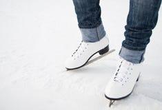 Pés da mulher nos patins de gelo brancos imagem de stock royalty free