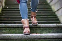 Pés da mulher que andam abaixo das escadas Imagens de Stock