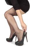 Pés da mulher que põem sobre sapatas dos saltos Foto de Stock Royalty Free