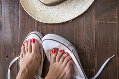 pés da mulher que põr sobre sapatas Fotografia de Stock