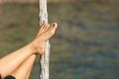 Pés da mulher que relaxam em feriados em uma praia ou em um lago Fotografia de Stock