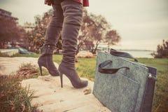 Pés da mulher que vestem botas e bolsa Fotografia de Stock