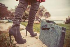 Pés da mulher que vestem botas e bolsa Fotografia de Stock Royalty Free