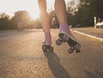 Pés da patinagem de rolo da jovem mulher no parque Fotos de Stock