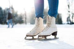 Pés da patinagem no gelo irreconhecível da mulher fora, perto acima imagem de stock