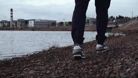 Pés da pessoa nas sapatilhas à moda que anda na costa rochosa na área urbana video estoque