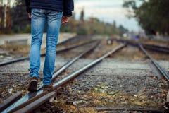 Pés da pessoa que andam em trilhas do trem Imagens de Stock
