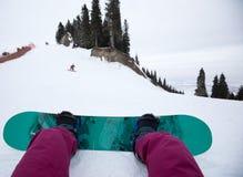 Pés da snowboarding em montanhas do inverno Fotos de Stock