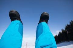 Pés da snowboarding em montanhas do inverno Foto de Stock