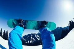 Pés da snowboarding na parte superior da montanha Imagens de Stock