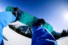 Pés da snowboarding na parte superior da montanha Imagem de Stock