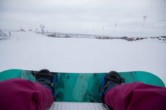 Pés da snowboarding na parte superior da montanha Foto de Stock