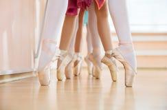 Pés das bailarinas novas que estão no pointe na fileira Fotos de Stock Royalty Free