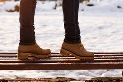 Pés das meninas do close up no banco no dia ensolarado do inverno no fundo borrado Passeio romântico no parque no vestuário do es imagens de stock royalty free